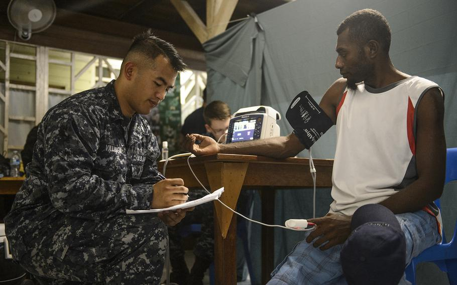Hospital Corpsman 2nd Class John Villanueva, assigned to the Military Sealift Command hospital ship USNS Mercy, takes a patient's blood pressure during a Pacific Partnership 2015 surgical screening at St. Mary's Hospital, July 6, 2015. Mercy was in Papua New Guinea for its second mission port of Pacific Partnership.   Mark El-Rayes/U.S. Navy