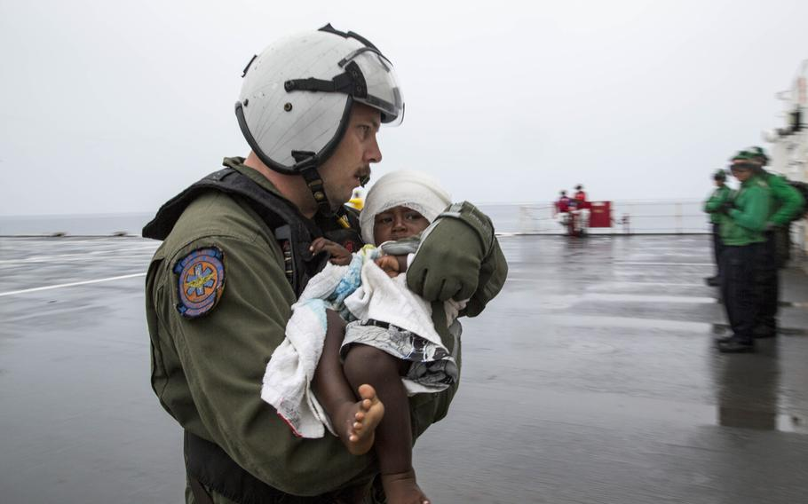 Hospital Corpsman 1st Class Matthew Hawkins, assigned to Helicopter Sea Combat Squadron 21, assists an infant aboard the Military Sealift Command hospital ship USNS Mercy June 30, 2015. Mercy launched one of its helicopters to transport six passengers, including one infant, who swam ashore after their ship sank off the coast of Carteret Island in Papua New Guinea.  Mercy was in Papua New Guinea as part of Pacific Partnership 2015.