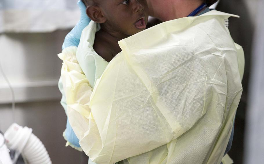 Cmdr. Marion Henry, a pediatric surgeon from San Diego, calms an infant in the casualty reception area of the Military Sealift Command hospital ship USNS Mercy, June 30, 2015. Mercy sent an MH-60S Sea Hawk helicopter on a critical care patient transport mission to retrieve six injured people, including an 18-month-old infant, from Han Island off the coast of Carteret Island in Papua new Guinea. Mercy was in Papua New Guinea for its second mission port of Pacific Partnership 2015.