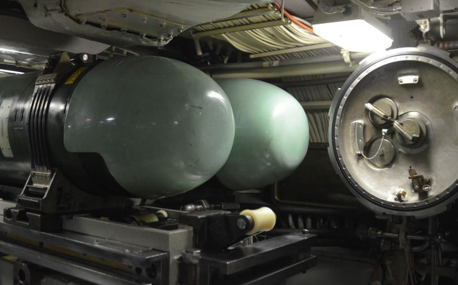 Two of the USS Michigan's Mk-48 torpedoes lie next to one of the submarine's tubes, as displayed during a port visit at Yokosuka Naval Base, Japan, on July 10, 2015. Two of the tubes can launch both torpedoes and Tomahawk cruise missiles. The two forward-most missile tubes were permanently converted to lock-out chambers that allow underwater deployment and retrieval of special operations personnel.