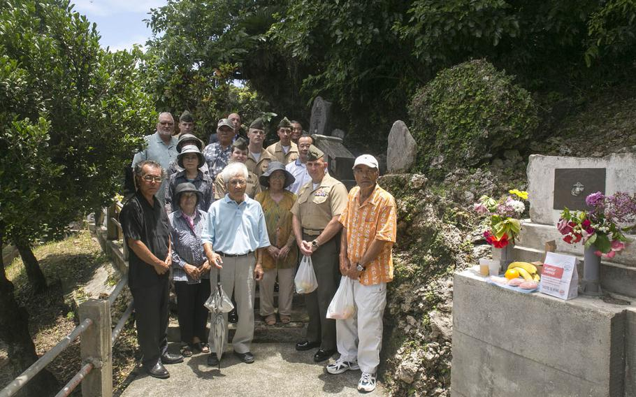 In this file photo from June 23, 2014, Marines and community members pose next to a memorial for Col. Kermit Shelly on Hamahiga Island, Okinawa, Japan. Infrastructure, including a reservoir that's still in use today, that Shelly and his Marines brought to Hamahiga in the 1960s was so appreciated by community members that a memorial was constructed for him following his death in 1968.