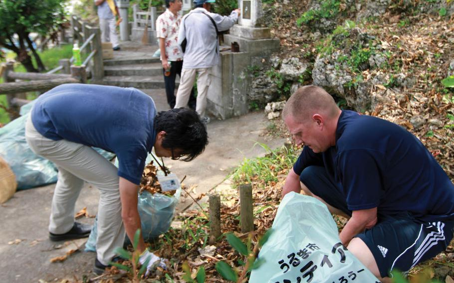 In this file photo from June 22, 2011, volunteers clean around Col. Kermit Shelly's memorial site on Hamahiga Island, Okinawa, Japan. Shelly, commanding officer of 3rd Force Service Regiment, known today as 3rd Force Service Support Group, helped bring much-needed infrastructure to the island in the late 1960s.