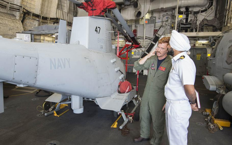 Lt. James Stranges, left, speaks Wednesday, Oct. 14, 2015, with an Indian navy officer about the MQ-8B Fire Scout drone during a tour of the USS Fort Worth as part of Exercise Malabar 2015.