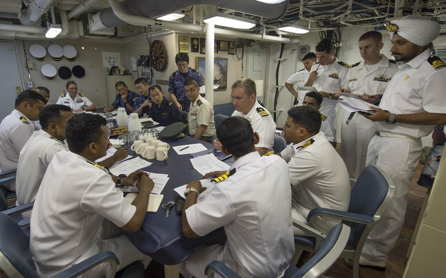 Officers from the U.S. and Indian navies and the Japan Maritime Self-Defense Force meet Monday, Oct. 12, 2015, on the USS Fort Worth ahead of Exercise Malabar 2015. Malabar, a series of complex, high-end war games that began in 1992, traditionally involves just the U.S. and India. Japan took part as a guest in the past and became a permanent member this year.