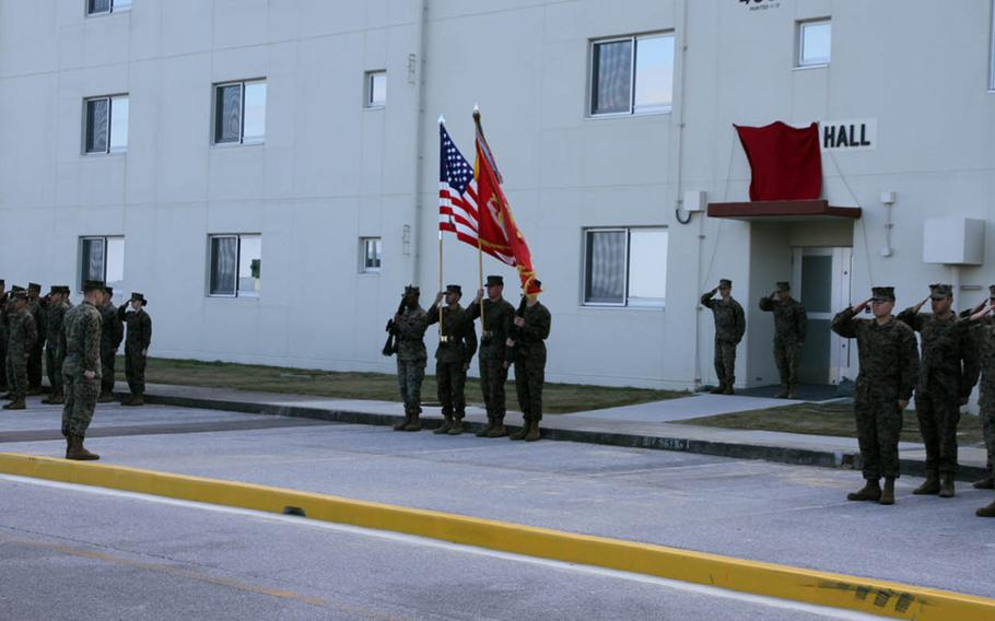Marines stand at attention during a ceremony to name a new barracks building at Camp Courtney, Okinawa, for Navy Cross recipient Marine Staff Sgt. Claude Dorris, Friday, Dec. 22, 2017.