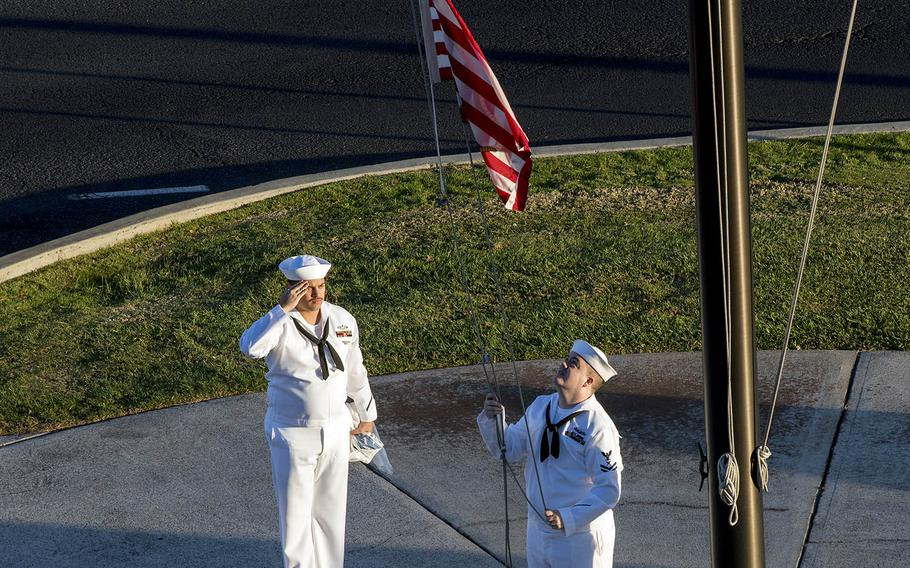 Petty Officer 2nd Class Gerado Taddei, left, and Petty Officer 2nd Class Andrew Thompson fly the First Navy Jack at Joint Base Pearl Harbor-Hickam, Hawaii, Monday, Jan. 1, 2018.