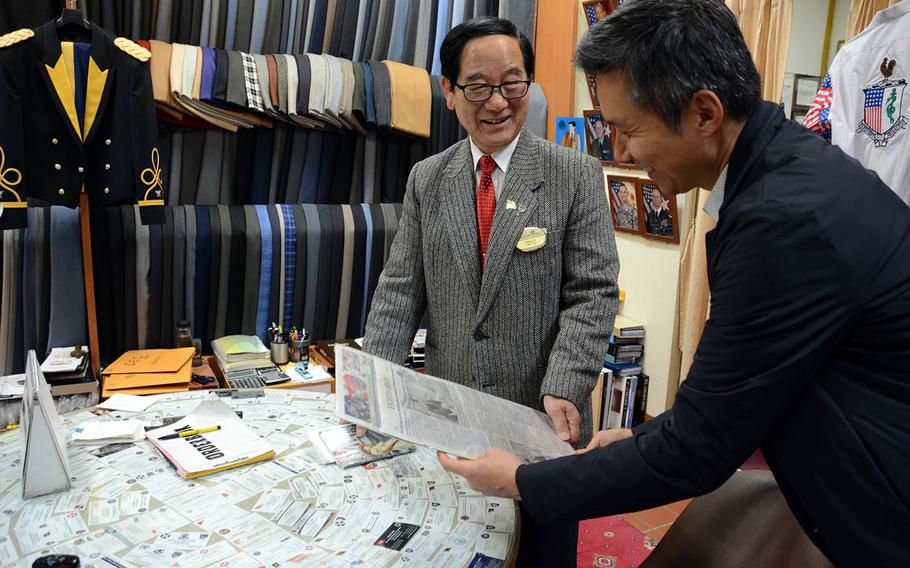 Chang Chin-kuk, left, owner of a tailoring company inside Dragon Hill Lodge at Yongsan Garrison, South Korea, speaks in December 2017 with Daniel Oh, co-founder of the Yongsan Legacy project.