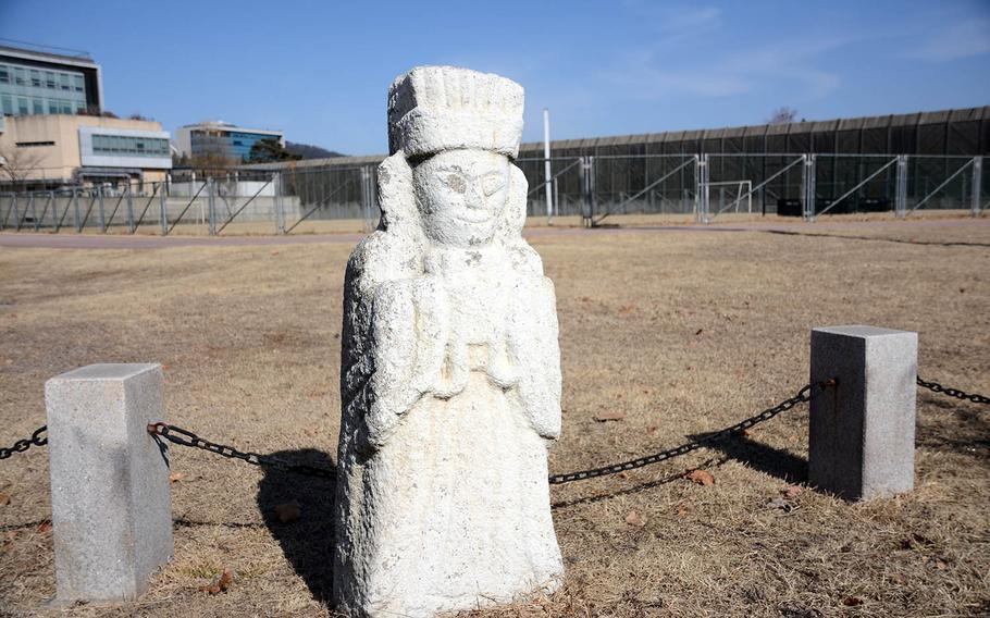 An ancient funerary statue near a running track at Yongsan Garrison, South Korea, serves as a reminder of the area's pre-military history.