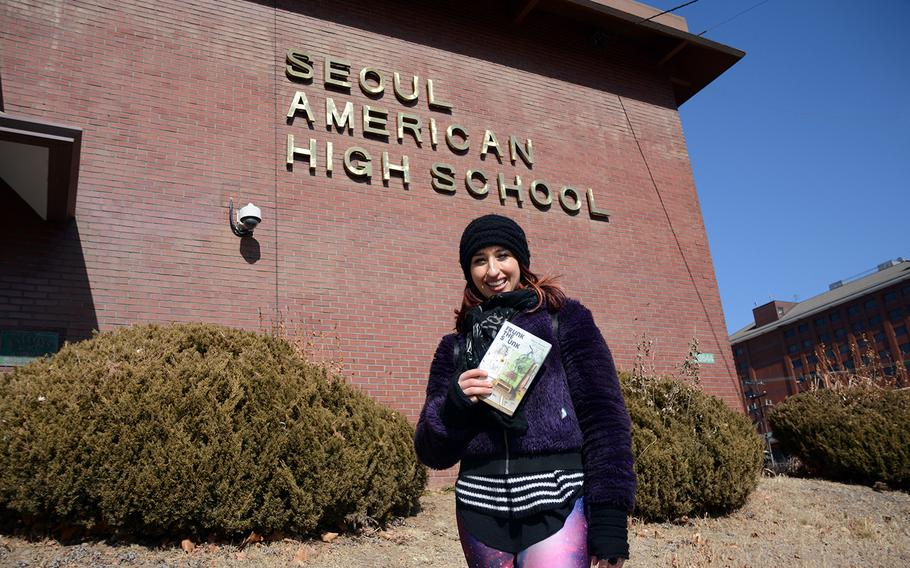 """Samia Mounts stands in front of Seoul American High School at Yongsan Garrison, South Korea, Saturday, Feb. 17, 2018. Her book, """"Frunk the Skunk,"""" is a young adult novel set on the base."""