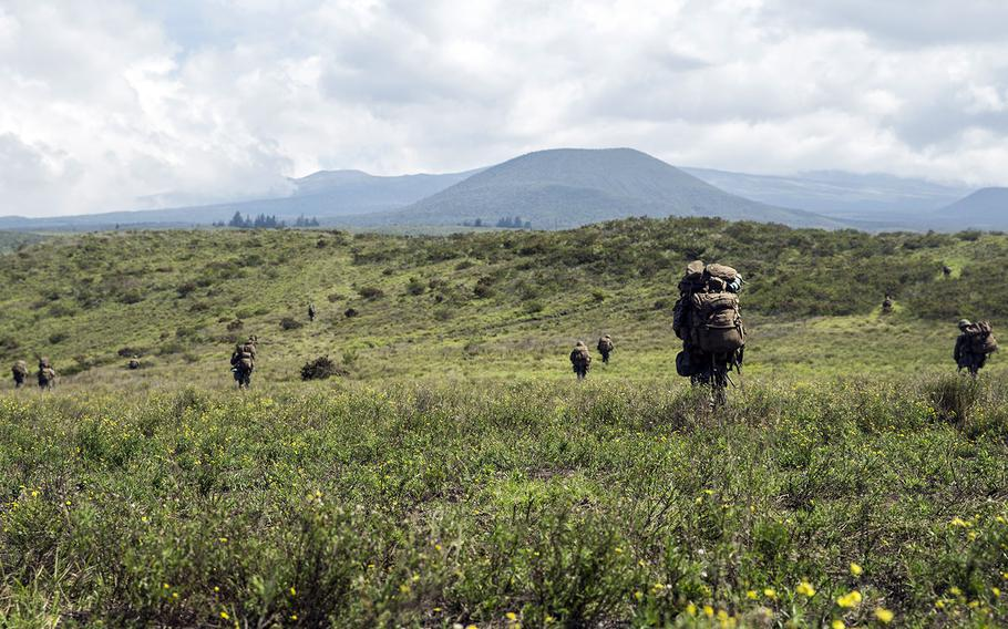 Marines with 2nd Battalion, 3rd Marine Regiment hike up a hill to dig fighting holes at the Pohakuloa Training Area on Hawaii Island, Oct. 31, 2017.