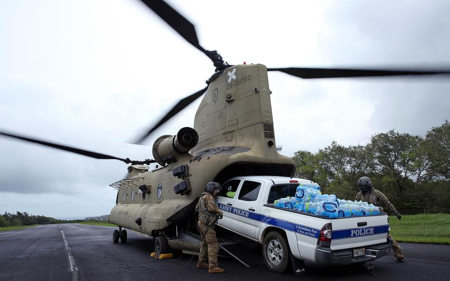 Soldiers from the 25th Combat Aviation Brigade, 25th Infantry Division load a law enforcement vehicle loaded with water onto a CH-47 Chinook, Tuesday, April 17, 2018, to assist in disaster-relief operations on the Hawaiian island of Kauai after severe rains, flooding and mudslides stranded hundreds of residents and tourists.