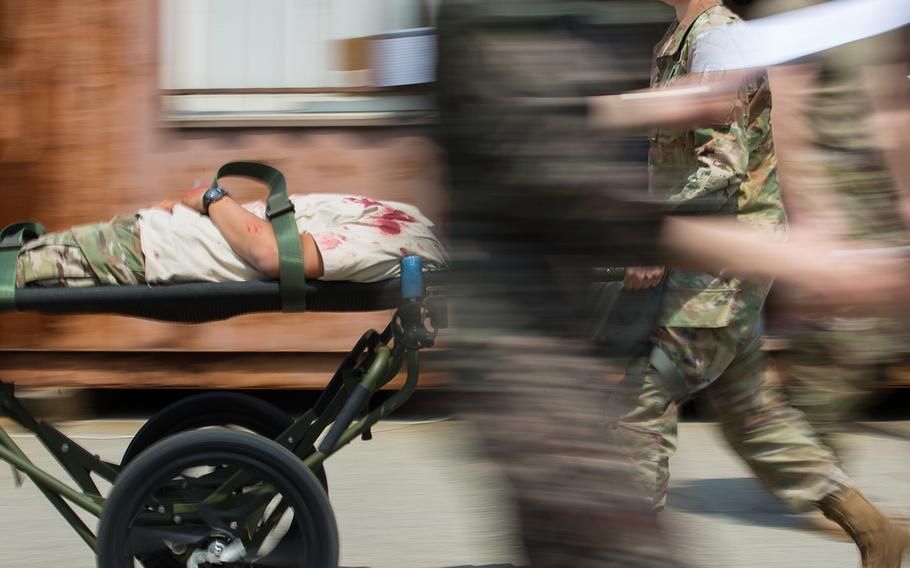 A medic rushes a patient during a mass casualty scenario at the 121st Combat Support Hospital at Camp Humphreys, South Korea, Friday, April 20, 2018.