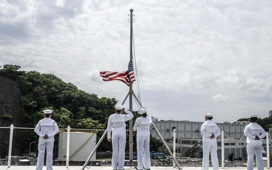 Sailors lower the flag to shift to underway colors as the USS Ronald Reagan departs Yokosuka Naval Base, Japan, Tuesday, May 29, 2018.