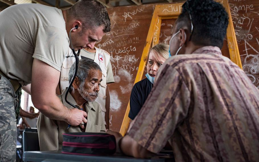 Airmen examine a patient while Marcelino Piedade, right, a translator from Dili, Timor-Leste, translates for the medical staff at the Negri Saran Kote Secondary School during Pacific Angel 2018 in Suai, Cova Lima Municipality, Southwest Timor-Leste, June 11, 2018.