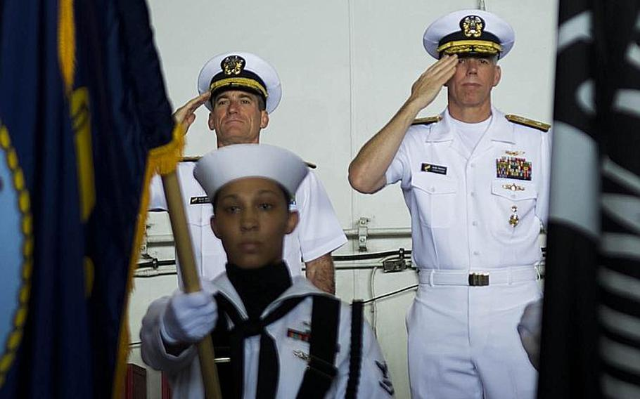 Rear Adm. Marc Dalton, left, and Rear Adm. Karl Thomas salute the colors during the Task Force 70 change-of-command ceremony aboard the USS Ronald Reagan in the Philippine Sea, Wednesday, July 18, 2018.