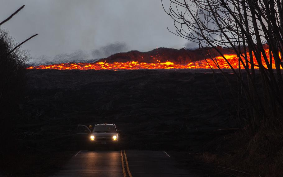 A U.S. Geological Survey vehicle drives away from a lava flow at Leilani Estates, Hawaii, Tuesday, July 17, 2018.