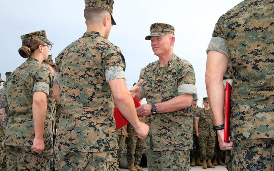 Lt. Gen. Lawrence Nicholson, III Marine Expeditionary Force commander, meritoriously promotes five Marines and a Navy corpsman at Camp Courtney, Okinawa, Thursday, Aug. 2, 2018.