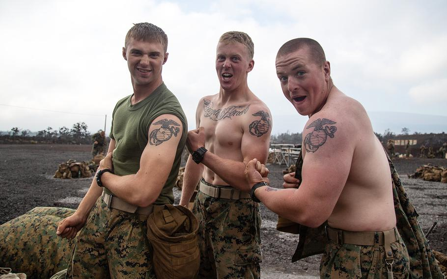 Left to right: Pfc. Larry Howdyshell, of Logan, Ohio; Lance Cpl. Brendan Clark, 19, of Lenexa, Kan.; and Pfc. Travis Stiles, 20, of  Queensbury, N.Y., show off their tattoos at Pohakuloa Training Area, Hawaii, Wednesday, July 18, 2018.
