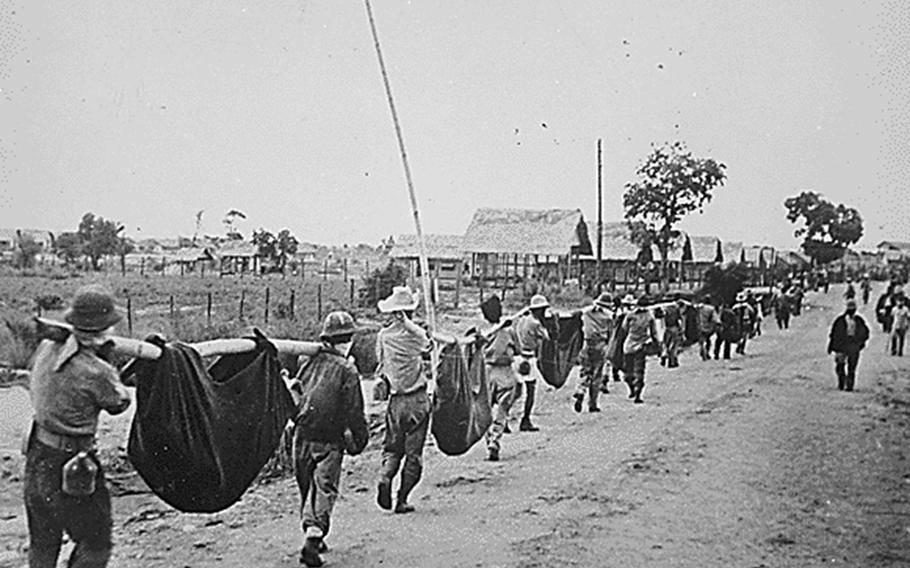 American and Filipino prisoners of war carry dead comrades after the Bataan Death March in May 1942.