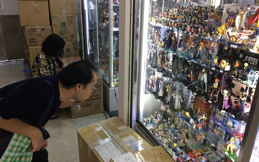 A customer gets a closer look at a display case featuring only a small sample of the many cases on display selling anime figurines at Nakano Broadway in Tokyo.