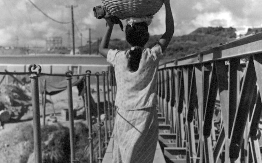 An Okinawan woman carries fish over a bridge in this photo taken by Army Capt. Charles Gail, who was stationed on the Japanese island prefecture in 1952 and 1953.