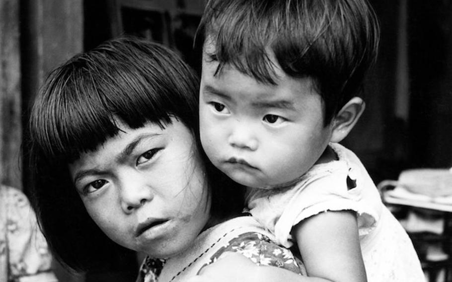 Masako Arakaki, 8, carries a boy on her back in this photo taken by Army Capt. Charles Gail, who was stationed on Okinawa in 1952 and 1953.