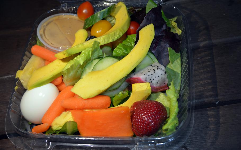 The Gourmet Sticky Rice kiosk in Honolulu piles its fruit salad high with large slices of papaya, avocado, dragon fruit and cucumber, along with strawberries, cherry tomatoes, and an egg atop a bed of romaine lettuce.