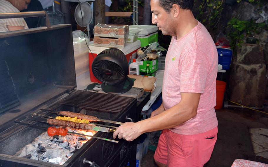 Kabab Nooni's Shahim Gholami tends to meat and tomato skewers over a bed of charcoal at a new food truck haven in Honolulu.