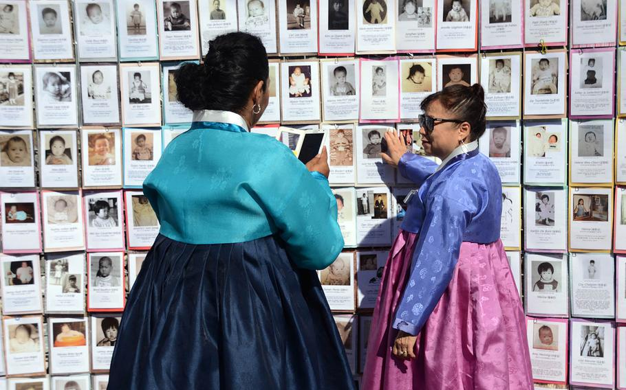 Sook Hee Scheibner, right, who was adopted from South Korea as a toddler, is photographed by a friend while pointing to a photo of herself as a baby on a memorial wall in Paju, South Korea, Sept. 12, 2018.