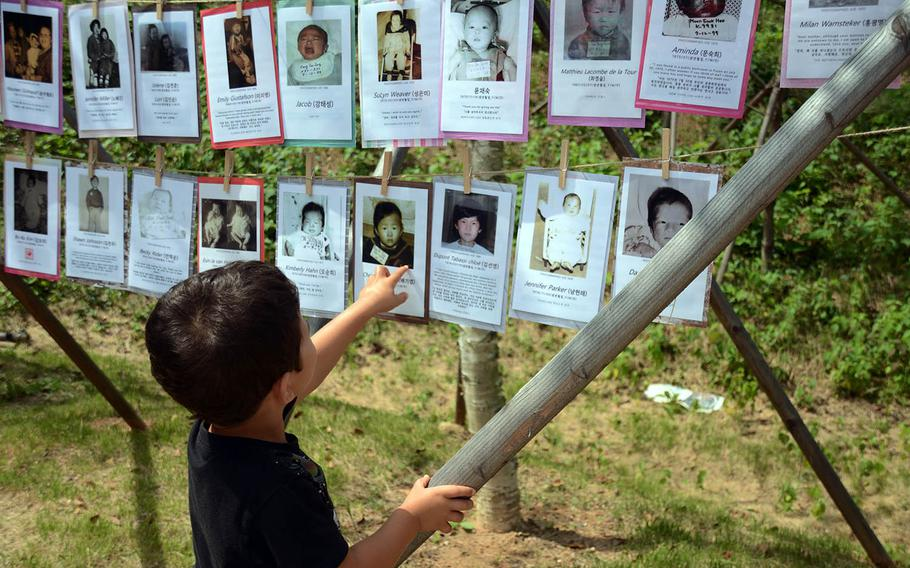 Garrett Nissen points to a baby picture of his father, Christian Nissen, who was adopted from South Korea, Sept. 12, 2018. The photos were part of a ceremony for a memorial park in Paju, South Korea.