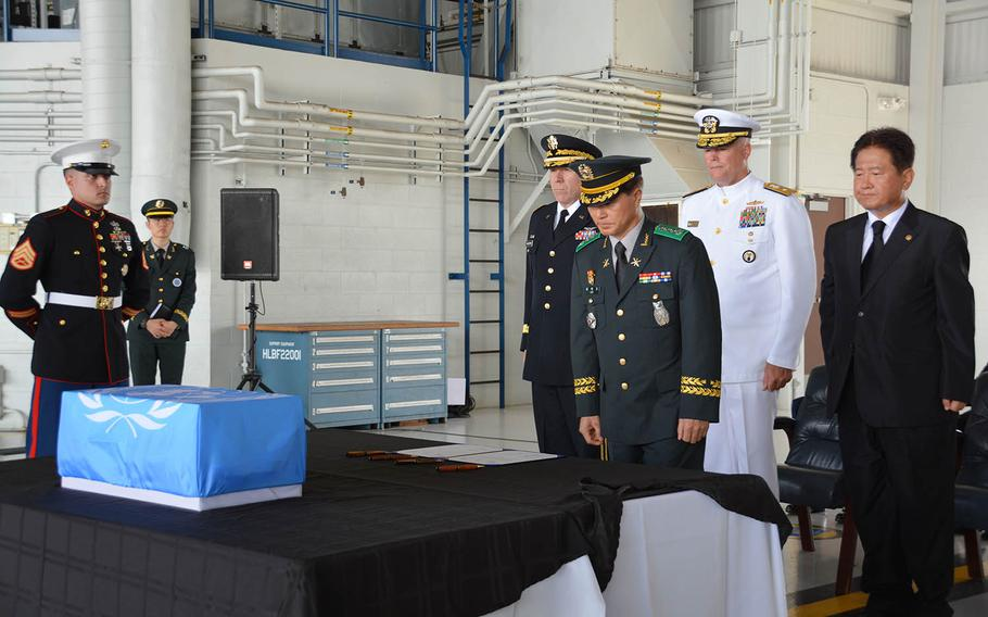 Col. Hak Ki Lee, commander of South Korea's KIA Recovery and Identification agency, bows before a box holding the remains of an unidentified South Korean soldier during a repatriation ceremony at Joint Base Pearl Harbor-Hickam, Hawaii, Thursday, Sept. 27, 2018. Standing behind him, from left, are United Nations Command Chief of Staff Maj. Gen. Mark Gillette; Rear Adm. Jon Kreitz, deputy director of the Defense POW/MIA Accounting Agency; and Choo Suk Suh, South Korea's vice minister of national defense.