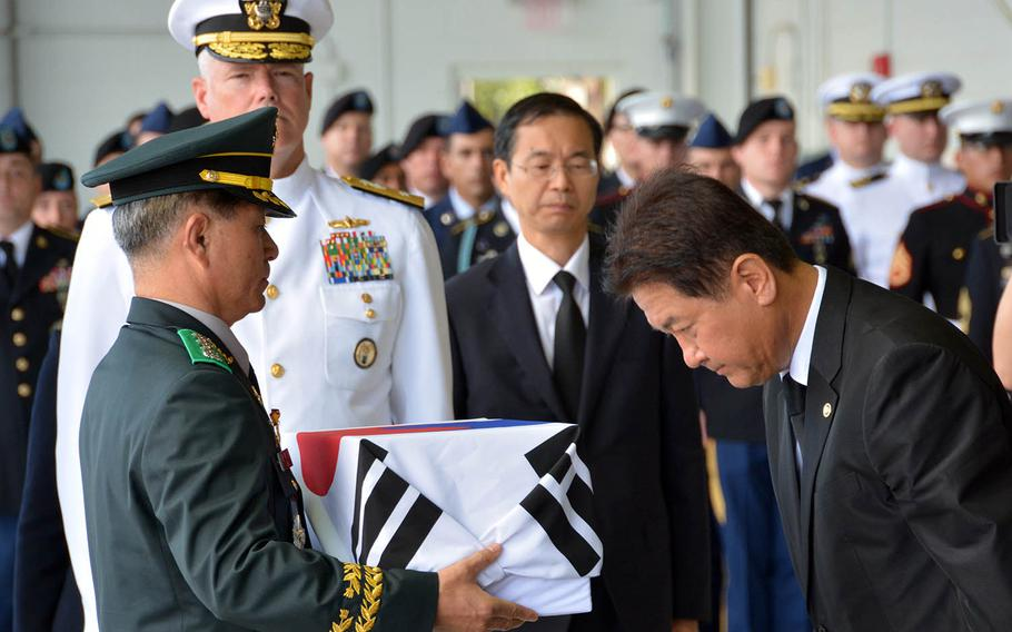 South Korean Vice Minister of National Defense Choo Suk Suh bows as he transfers a box of remains to Col. Hak Ki Lee, commander of the KIA Recovery and Identification agency, during a repatriation ceremony at Joint Base Pearl Harbor-Hickam, Hawaii, Thursday, Sept. 27, 2018.