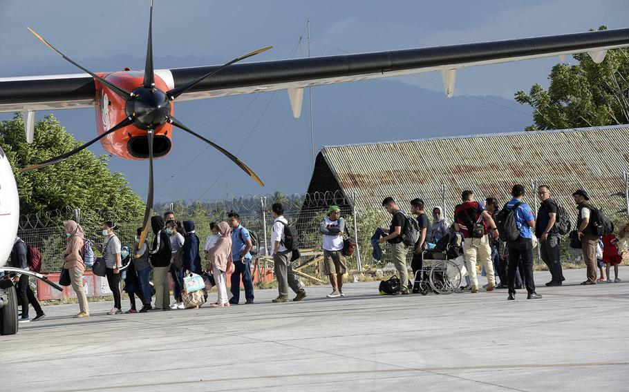 Evacuees prepare to board aircraft in Palu, Indonesia, Oct. 6, 2018. Thousands were displaced after a 7.5-magnitude earthquake and tsunami struck on Sept. 28, 2018.