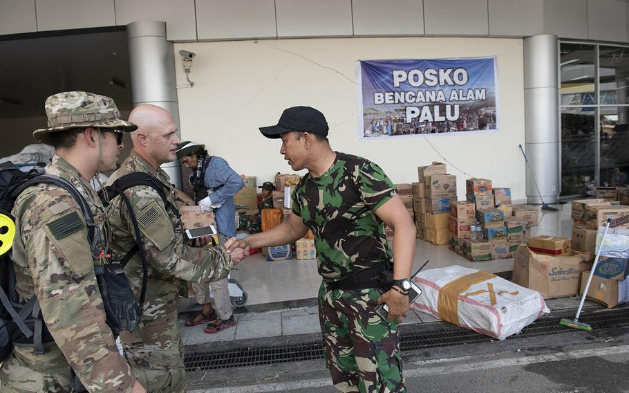 Air Force Lt. Col. Aaron Lane, 36th Mobility Response Squadron commander, center, and Maj. Sean Conley, 36th MRS operations officer, are greeted by an Indonesian servicemember in Palu, Indonesia, Oct. 6, 2018.
