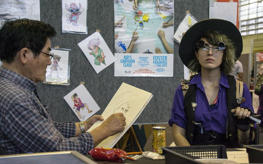 An artist draws a portrait of a cosplayer during Comic Con Okinawa hosted by the Marine Corps Community Services at Camp Foster, Sunday, Oct. 14, 2018.