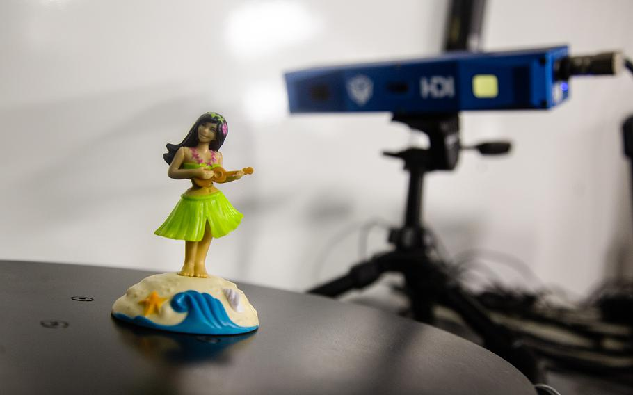 A plastic hula girl is set aside for scanning inside the Army's Rapid Fabrication via Additive Manufacturing on the Battlefield facility at Camp Humphreys, South Korea, Monday, Oct. 29, 2018.