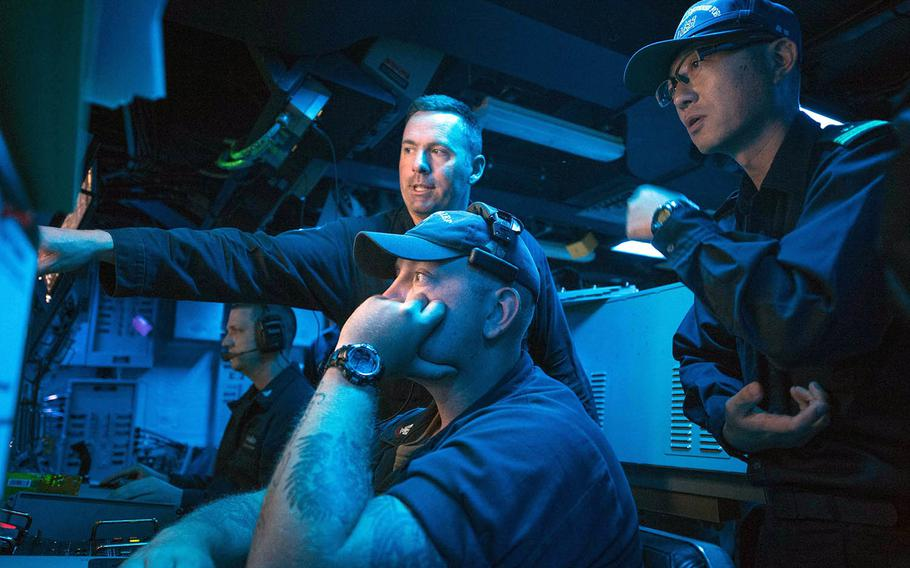 Lt. Cmdr. William Russell and Petty Officer 2nd Class Joseph Larsen of the mine-countermeasures ship USS Chief demonstrate the ship's sonar capabilities to Lt. Cmdr. Akihiko Morita of the Japan Maritime Self-Defense Force during July drills off Aomori prefecture.