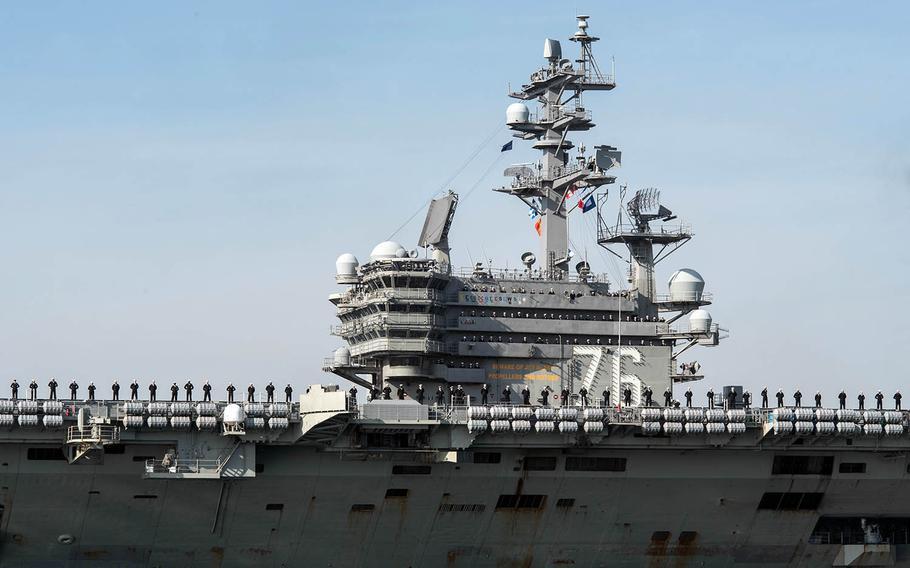 Sailors man the rails as the USS Ronald Reagan arrives at Yokosuka Naval Base, Japan, after a patrol in December 2017.