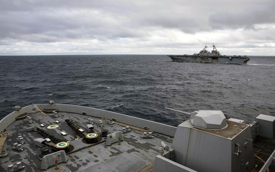 The amphibious assault ship USS Wasp, background, and the amphibious transport dock ship USS Green Bay steam in the East China Sea on Friday, Jan. 12, 2019.