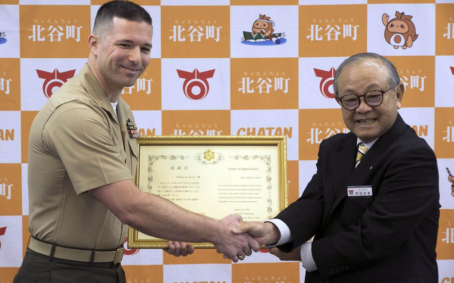 Marine Maj. William Easter, left, of the III Marine Expeditionary Force on Okinawa, receives a letter of appreciation Tuesday, Jan. 22, 2019, from Chatan Mayor Masaharu Noguni for a rescue at sea in December.
