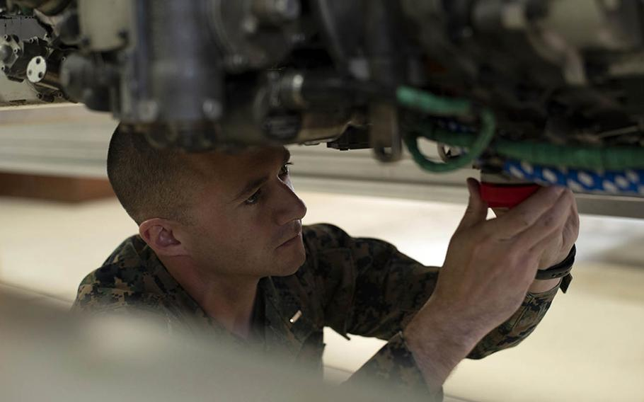First Lt. Simon Miller of Marine Aviation Logistics Squadron 12 at Marine Corps Air Station Iwakuni, Japan, demonstrates the installation of drain plugs that are part of an engine ship kit he designed and built using a 3D printer, Nov. 29, 2018.
