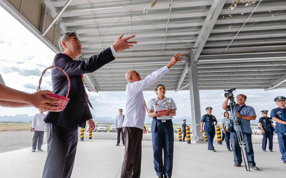 U.S. Ambassador Sung Y. Kim and Philippine Defense Secretary Dlfin Lorenzana toss coins Tuesday, Jan. 29, 2019,  at the Basa Air Base Humanitarian Assistance and Disaster Relief warehouse, symbolizing good fortune for the new building.