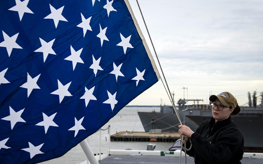 Petty Officer 2nd Class Taylor Miller unfurls the union jack on the jack staff of the aircraft carrier USS Dwight D. Eisenhower in this undated Navy photo.