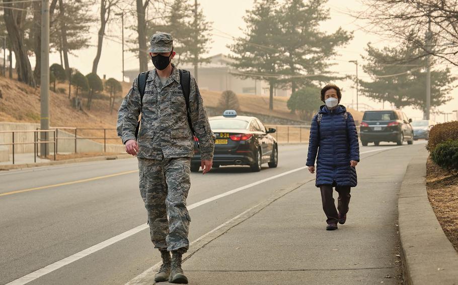 Pedestrians wear air-filtering masks at Osan Air Base, South Korea, Wednesday, March 6, 2019.