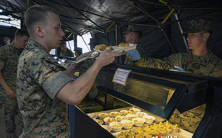 A Marine receives a build-your-own Okinawa taco rice meal entered in for judging during the W.P.T. Hill award competition at Camp Kinser, Okinawa, Japan, on March 14, 2019.