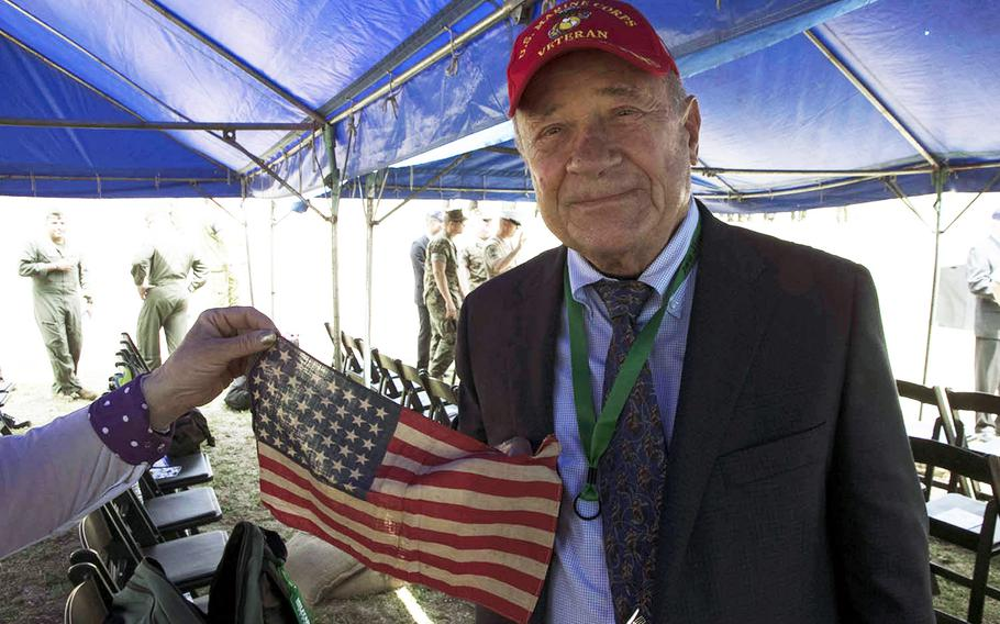 Retired Marine Capt. Robert W. Van Camp on March 23, 2019, during a 74th anniversary ceremony holds a flag that was carried by his father, Gunnery Sgt. Robert Van Camp, during the Battle of Iwo Jima, Japan, in February 1945.