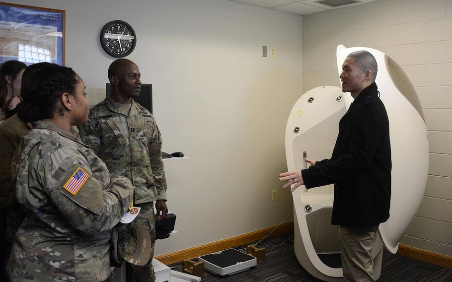 Soldiers listen as John Sim, right, director of the new Army Wellness Center at Camp Humphreys, South Korea, explains how to use the BOD POD, which measures body fat and muscle composition, Friday, March 22, 2019.