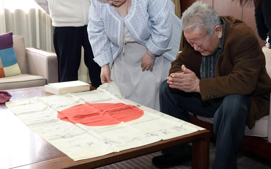 Jitsuo Matsue prays over a flag carried by his father, Hisao Matsue, during World War II, after it was returned to his family at the town hall in Kamigori, Japan, March 17, 2019.
