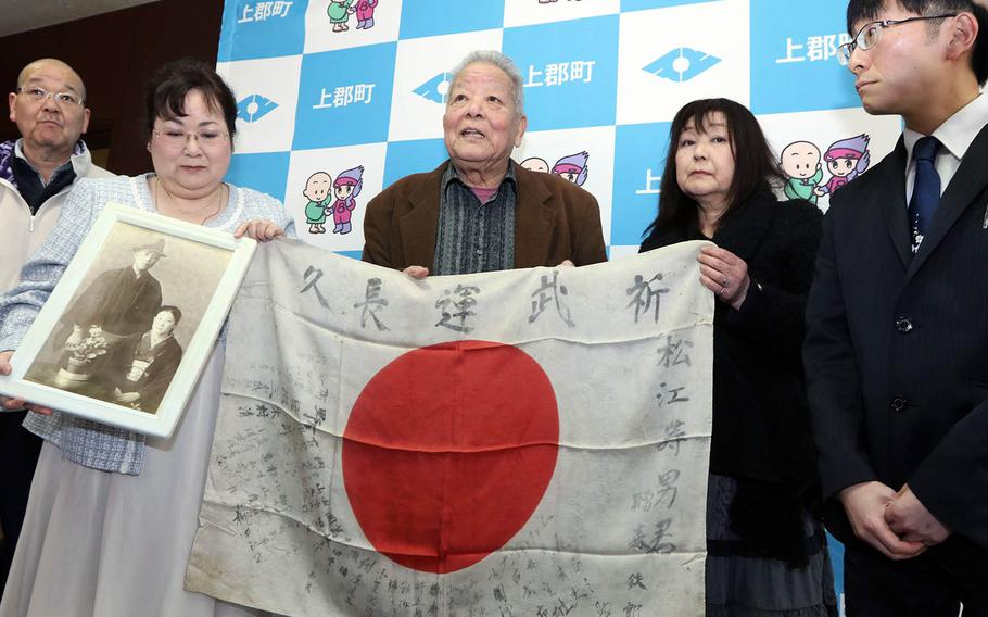 The family of Hisao Matsue holds the Japanese flag he carried during World War II after it was returned to them at the town hall in Kamigori, Japan, March 17, 2019.