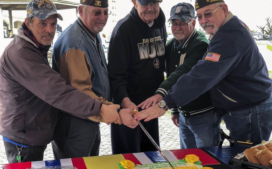 Veterans use a ceremonial sword to cut a cake that honors National Vietnam War Veterans Day at Yokosuka Naval Base, Japan, Friday, March 29, 2019.